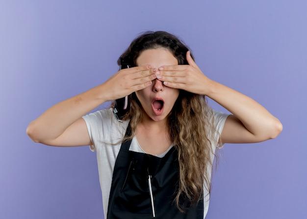 Mujer joven peluquero profesional en delantal que cubre los ojos con las manos
