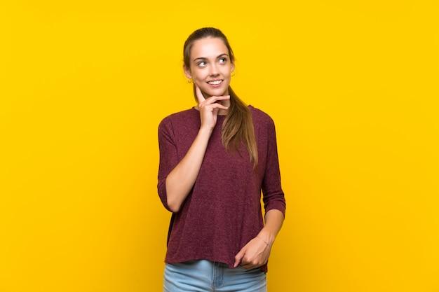 Mujer joven pensando una idea mientras mira hacia arriba