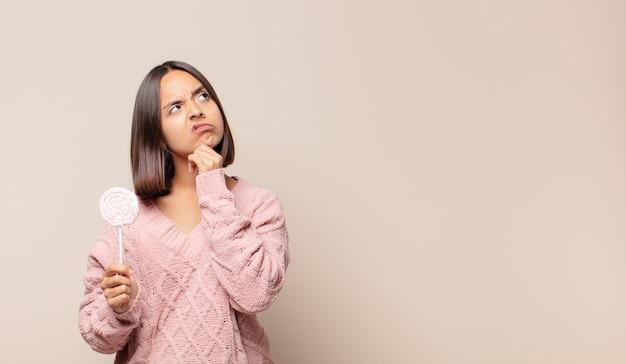 Mujer joven pensando, sintiéndose dudoso y confundido, con diferentes opciones, preguntándose qué decisión tomar