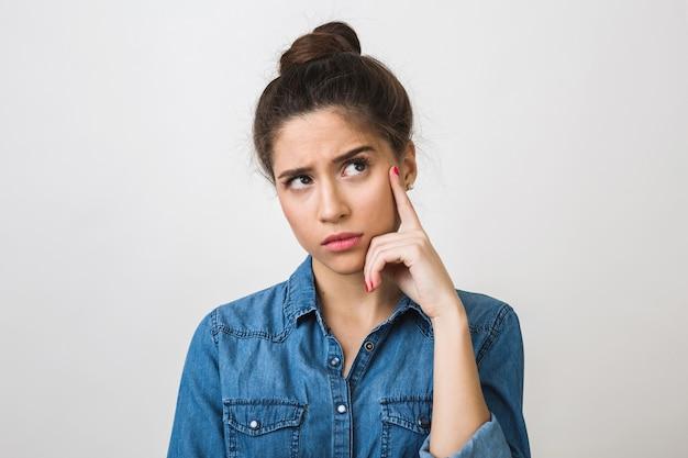Mujer joven pensando, sosteniendo el dedo en su sien, mirando hacia arriba, elegante camisa de mezclilla,