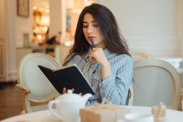 Mujer joven pensativa con bloc de notas y pensando en ideas creativas para escribir ensayos en un café