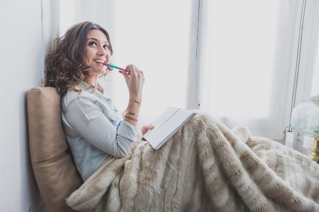 Mujer joven pensativa con un bolígrafo en la boca
