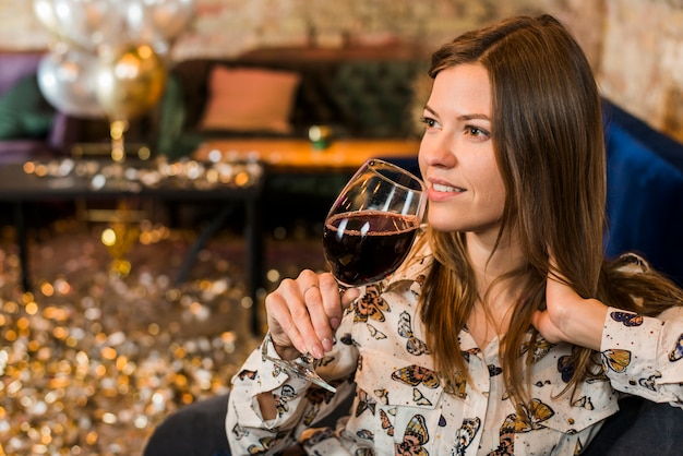 Mujer joven pensativa con la copa de vino en barra