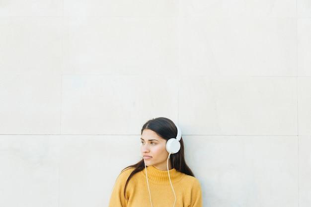 Mujer joven pensativa escuchando música de pie contra la pared blanca