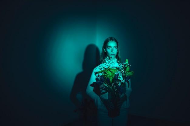 Mujer joven pensativa con flores en florero