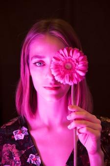 Mujer joven pensativa con gerbera rosa