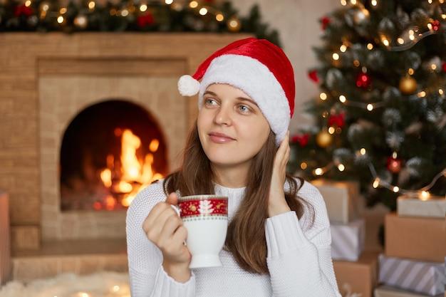 Mujer joven pensativa con gorro de papá noel junto al árbol de navidad y la chimenea en casa, mirando soñadoramente a un lado, sosteniendo la taza con café o té, vistiendo un suéter blanco cálido.