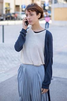 Mujer joven pensativa hablando por teléfono inteligente