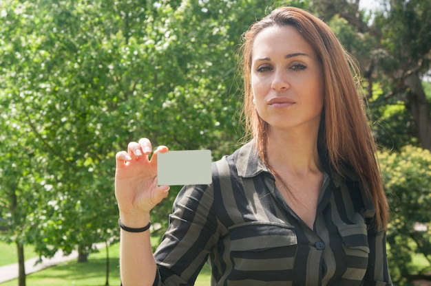 Mujer joven pensativa hermosa que sostiene la tarjeta de visita