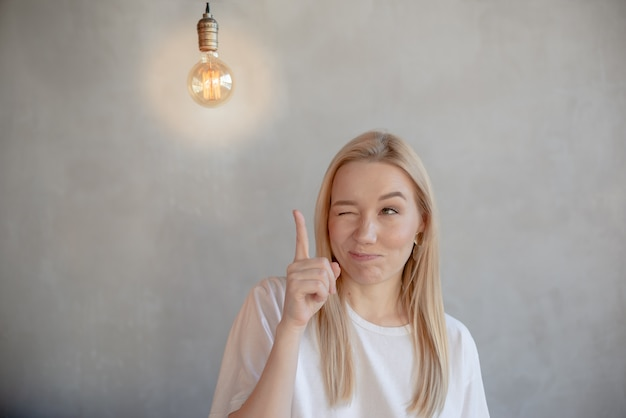 Mujer joven pensativa mirando brillantes bombillas. vista horizontal negocios y concepto de idea copyspace. chica reuniendo ideas, concepto de pensamiento de éxito