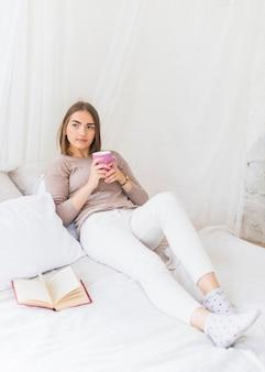 Mujer joven pensativa que sostiene la taza de café rosada en la mano que se sienta en cama