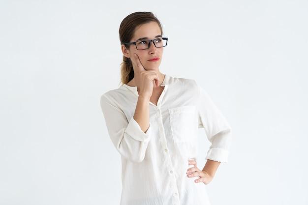 Mujer joven pensativa que toca la cara con el dedo y que mira lejos.