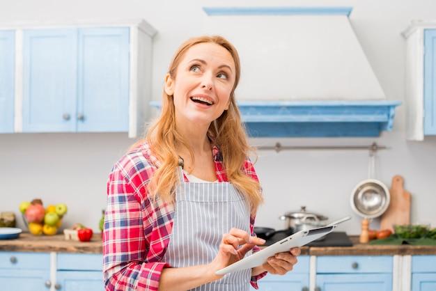 Mujer joven pensativa que usa la tableta digital en la mano que se coloca en la cocina