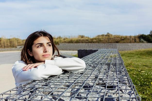 Mujer joven pensativa y relajada sentada en un parque público mientras mira lejos