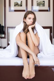 Mujer joven pensativa está sentada con una manta sobre su cabeza en la cama con ropa de cama blanca, concierto de hotel, apartamento moderno