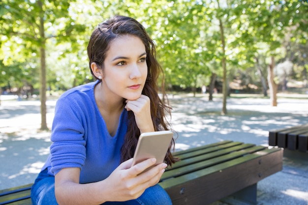 Mujer joven pensativa con smartphone en el parque