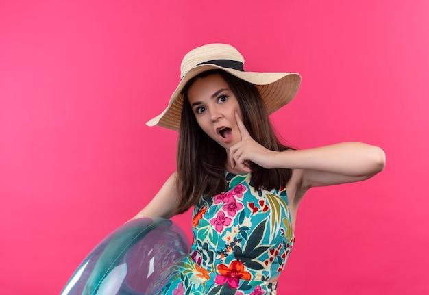 Mujer joven pensativa con sombrero sosteniendo el anillo de natación y poniendo el dedo en la cara en la pared rosa aislada