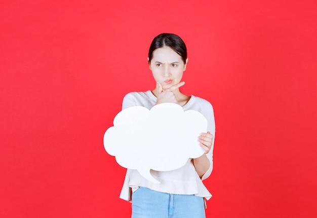 Mujer joven pensativa sosteniendo bocadillo con forma de nube