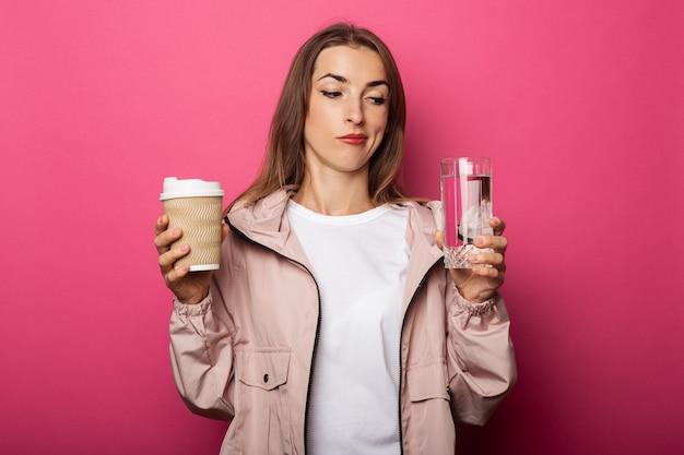 Mujer joven pensativa sosteniendo vaso de papel y vaso con agua