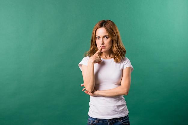 Mujer joven pensativa con su dedo en los labios contra fondo verde