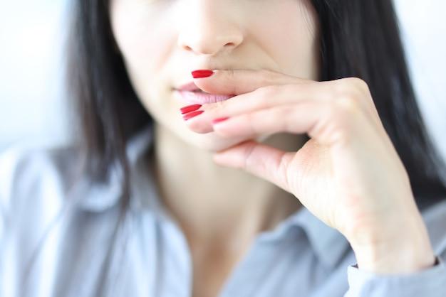 Mujer joven pensativa tocando los labios con las manos con primer plano de manicura rojo