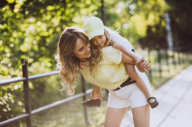 Mujer joven con pequeña hija caminando en el parque