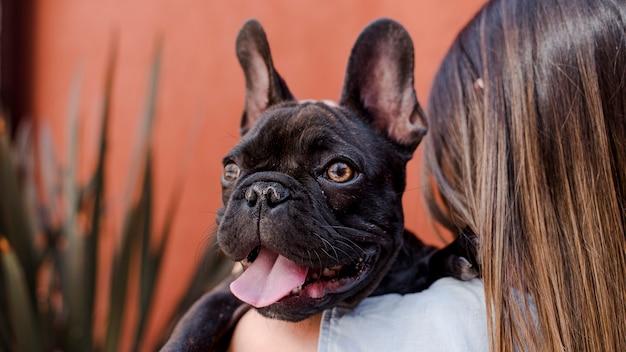 Mujer joven con pequeño bulldog francés