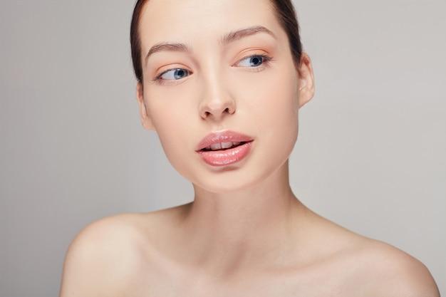 Mujer joven perfecta con piel limpia y fresca mirando hacia el lado