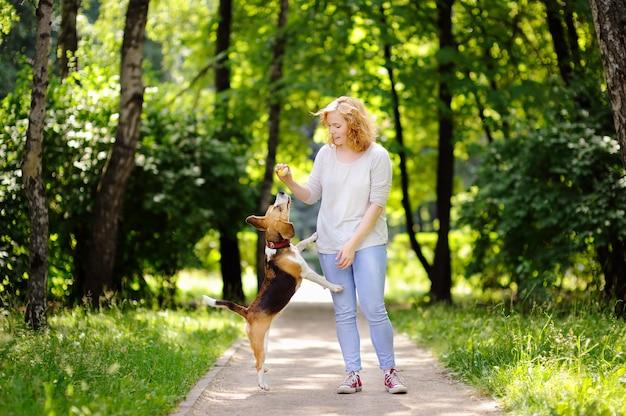 Mujer joven con el perro del beagle en el parque del verano. mascota obediente con su dueño practicando el comando de salto.