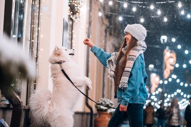 Mujer joven y un perro blanco que muestra trucos en una calle