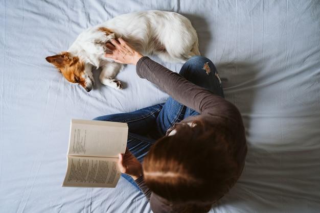 Mujer joven y perro en casa descansando sobre la cama.