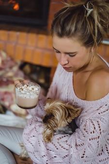 Mujer joven con un perro cerca de la chimenea bebe cacao con malvaviscos.