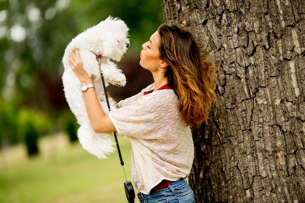 Mujer joven con un perro maltés