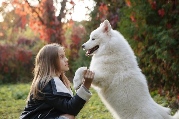 Mujer joven con un perro a pasear por el parque