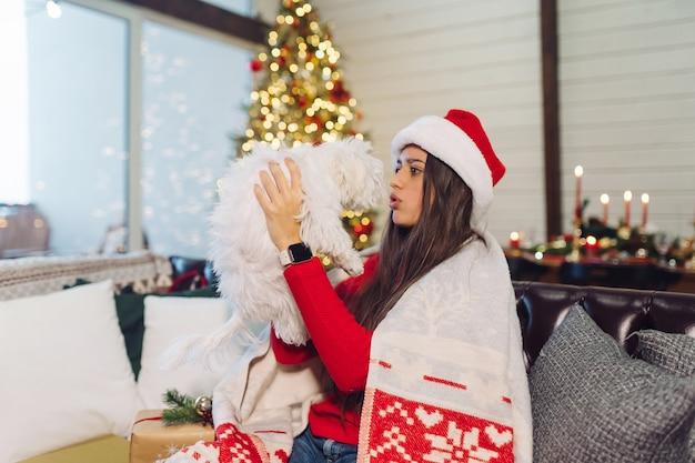 Mujer joven con un perro pequeño en sus brazos se sienta en el sofá en la víspera de año nuevo
