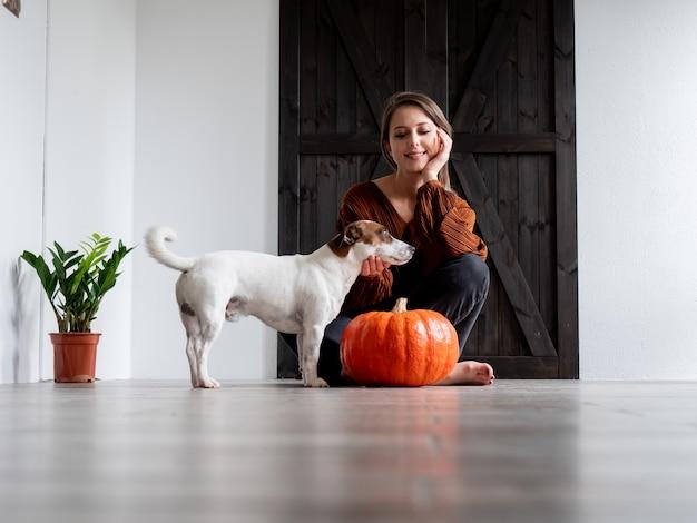 Mujer joven con perro y punkin sentado en el suelo