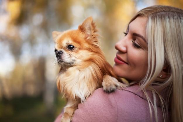 Mujer joven con perro en sus brazos en el fondo de la hermosa naturaleza