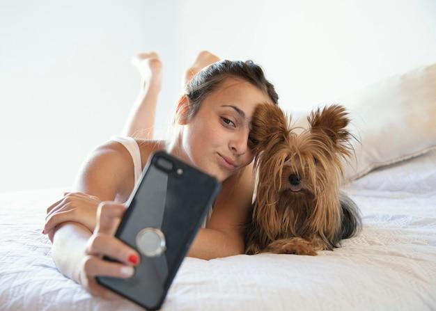 Mujer joven con perro tomando selfie
