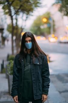 Mujer joven, persona en máscara protectora médica estéril en calle vacía