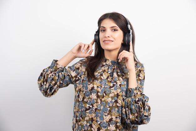 Mujer joven de pie con auriculares sobre fondo blanco.