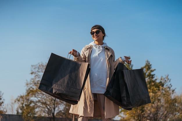 Una mujer joven está de pie en un automóvil con bolsas en las manos