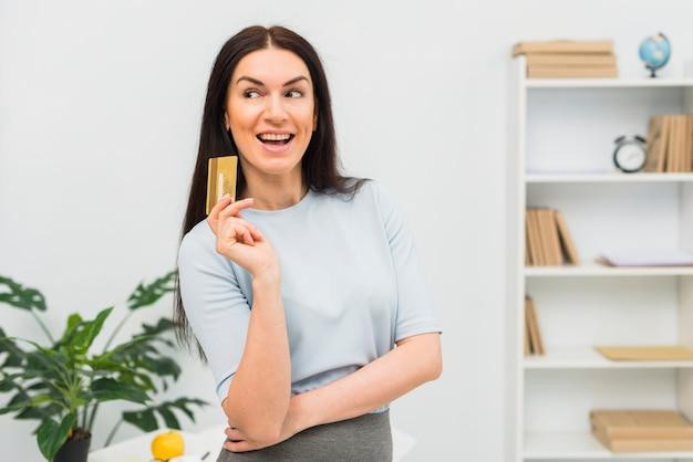 Mujer joven en pie azul con tarjeta de crédito en la oficina
