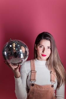 Mujer joven de pie con bola de discoteca