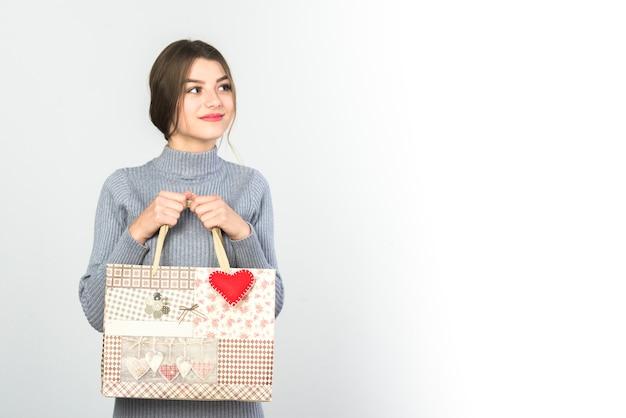 Mujer joven de pie con bolsa de regalo