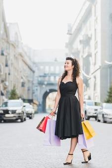 Mujer joven de pie con bolsas de compras en la calle