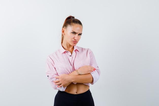 Mujer joven de pie con los brazos cruzados en camisa casual, pantalones y mirando confiado