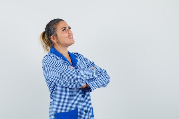Mujer joven de pie con los brazos cruzados en camisa de pijama de cuadros vichy azul y luciendo bonita. vista frontal.