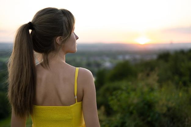 Mujer joven de pie en el campo verde disfrutando de la vista del atardecer en la naturaleza de noche.