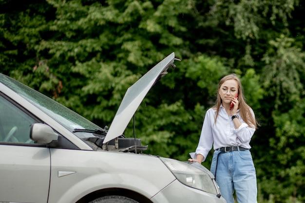 Mujer joven de pie cerca de coche averiado con apareció