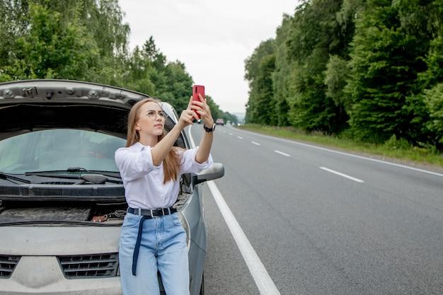 Mujer joven de pie cerca del coche averiado con el capó levantado que tiene problemas con su vehículo.